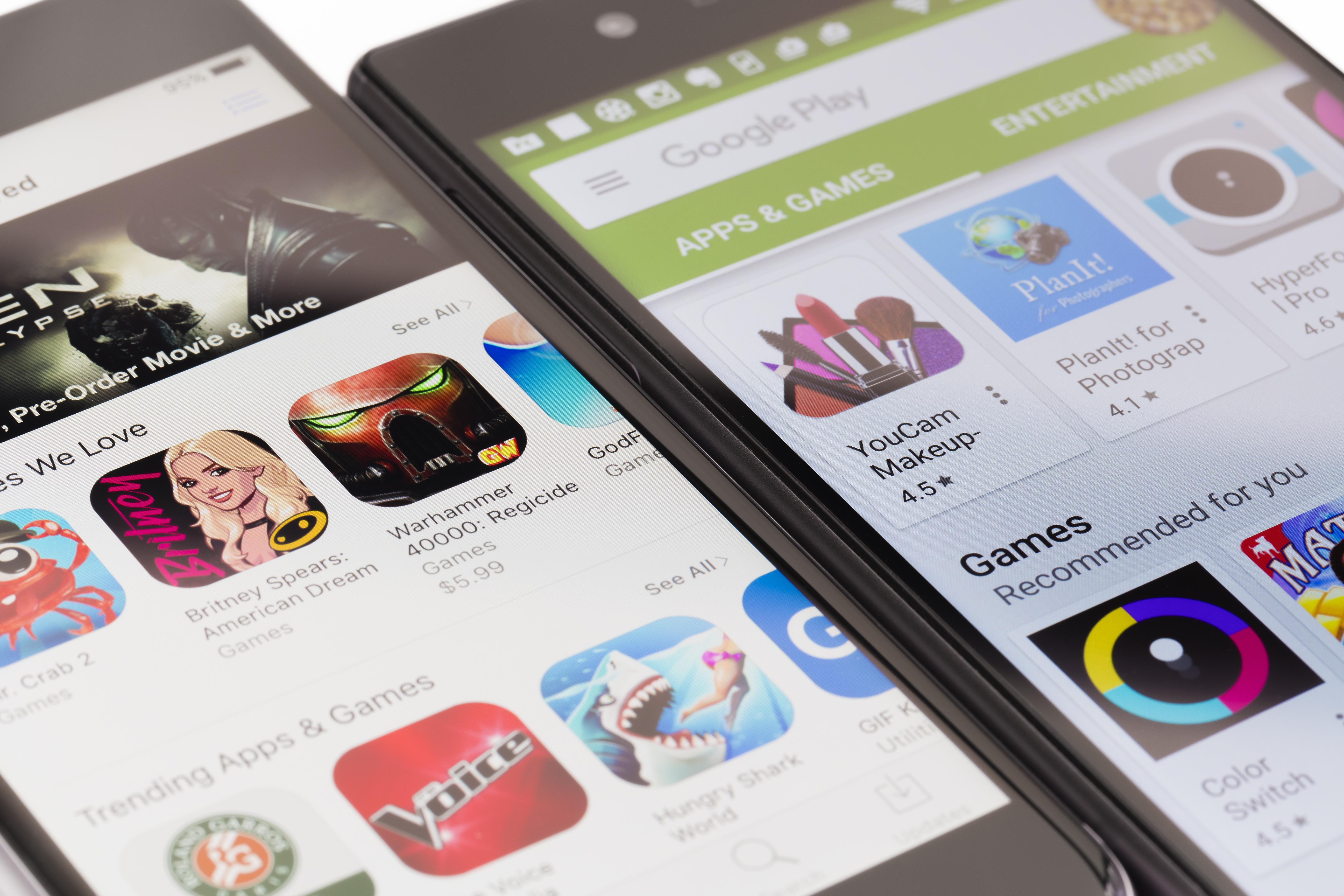 Melbourne, Australia - May 23, 2016: Close-up view of Google Play Store on Android smartphone and Apple's App Store on iPhone. Both stores allow users to download app, music, movies and TV shows.